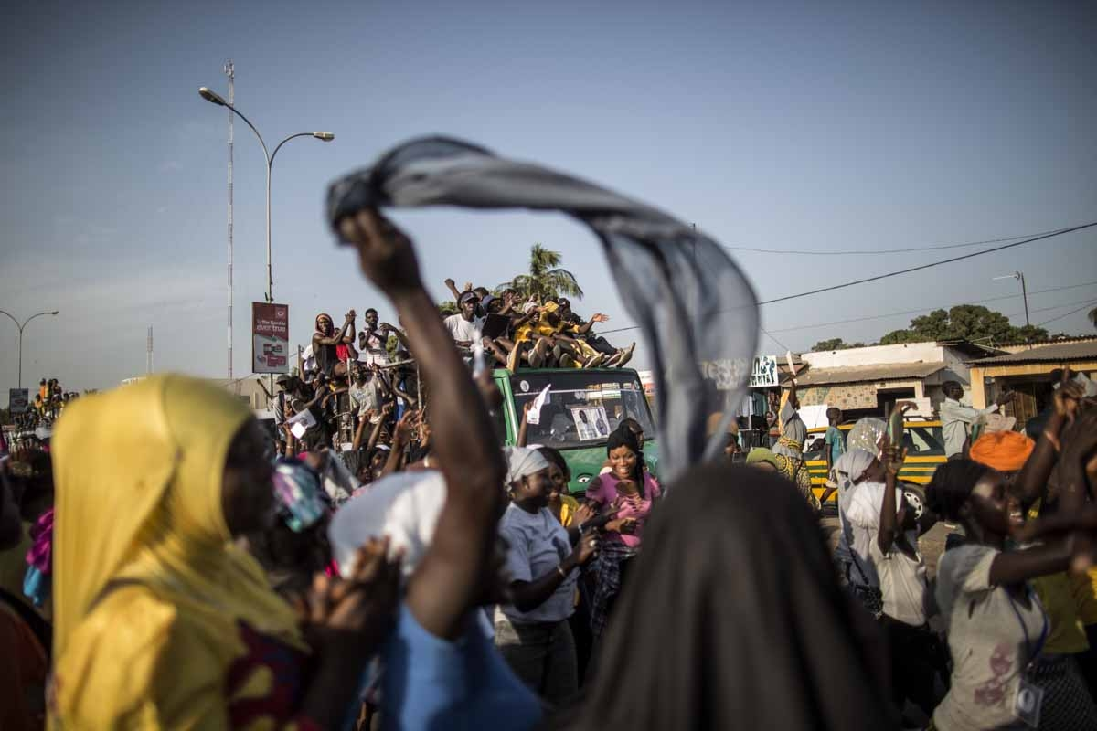 Supporters of Adama Barrow, the flag-bearer of the coalition of the seven opposition political parties in Gambia, gather in the streets of Talinding on the outskirts of Banjul on November 25, 2016 to try to catch a glimpse of the candidate motorcade trans