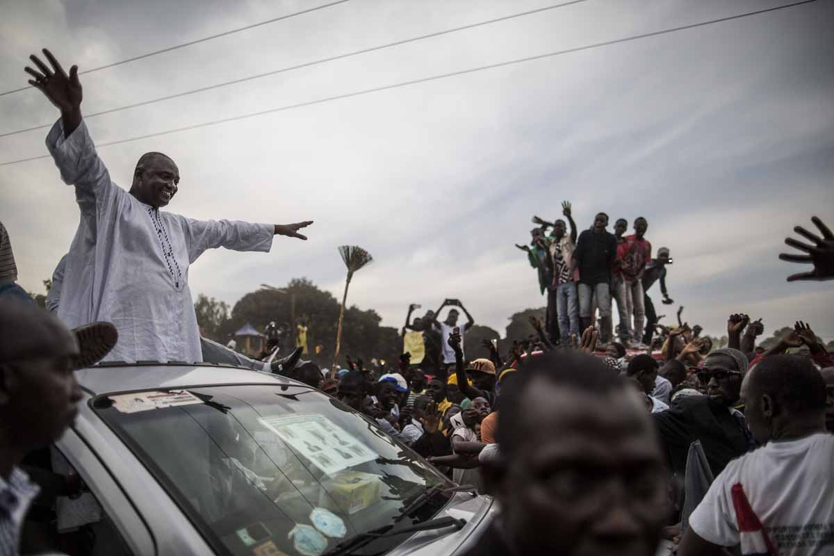 Adama Barrow, the flag-bearer of the coalition of the seven opposition political parties in Gambia, greets supporters from the roof of his car at a gathering in the buffer Zone district of Talinding on November 29, 2016 on the last day of the presidential