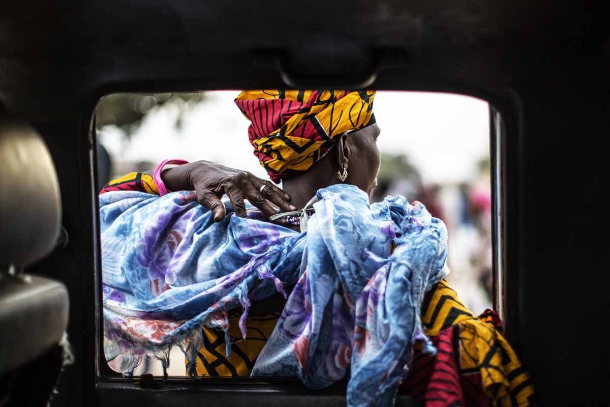 A supporters of Adama Barrow, the flag-bearer of the coalition of the seven opposition political parties in Gambia, leans on the door of a car in the Buffer Zone district of Talinding on November 29, 2016 on the last day of the presidential campaign in Ga