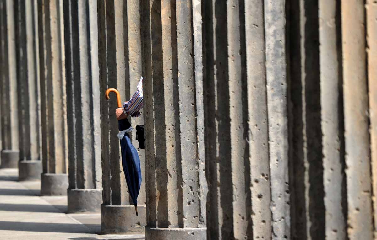 A man carries an umbrella as he walks past columns on the museum island on August 2, 2010 in Berlin. Weahter was unsettled with sinking temperatures and rain in the German capital.