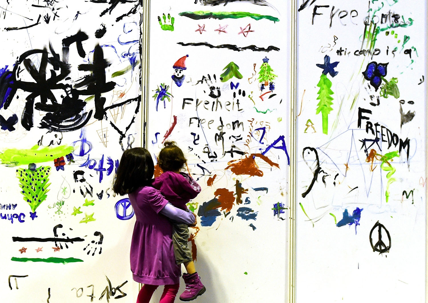 Young refugees pass by a painted wall of a temporary bedroom at a refugee accomodation hosted in a hangar of the former Tempelhof airport in Berlin on December 26, 2015
