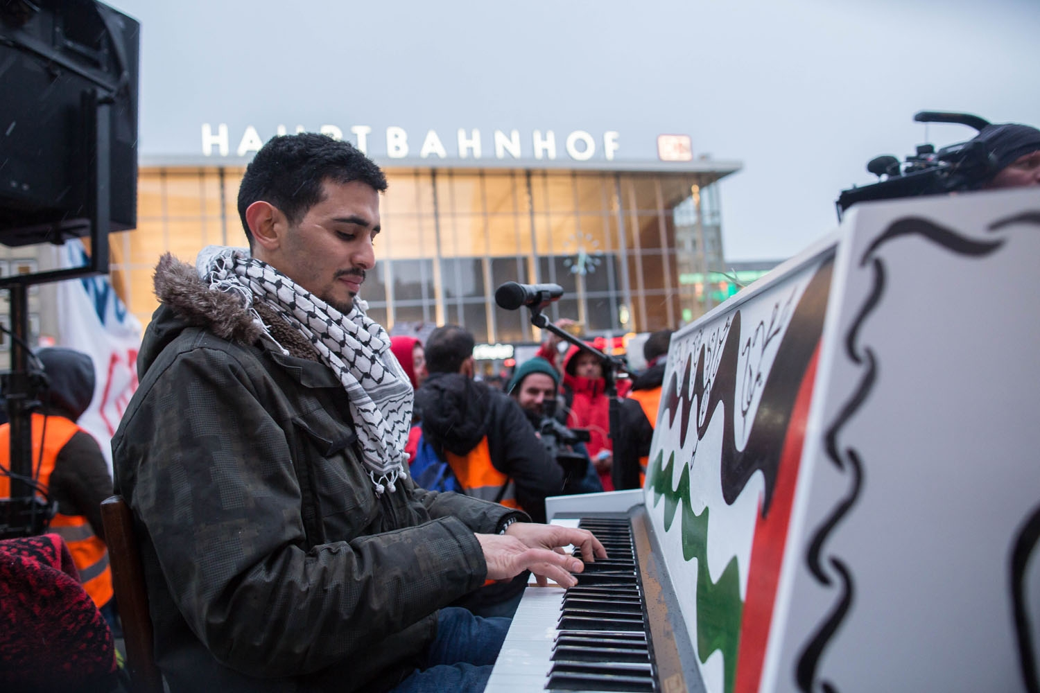 Syrian-Palestinian pianist Aeham Ahmad plays the piano during a demonstration of Syrian refugees against violence on January 16, 2016 in Cologne, western Germany