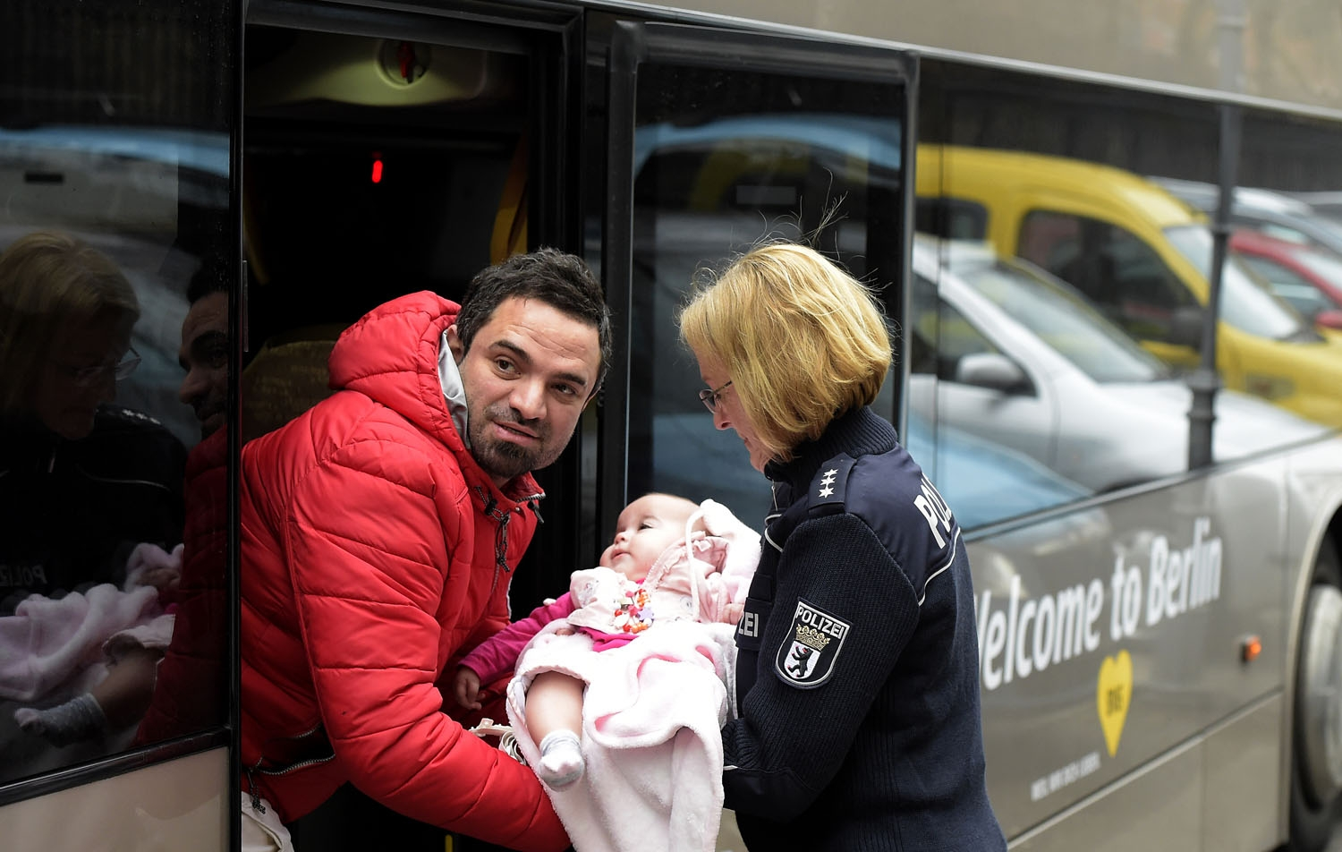 A German police woman helps a man carrying a baby into a bus outside the registration office of the State Office of Health and Social Affairs (LAGeSo) in Berlin on March 11, 2016. / AFP PHOTO / TOBIAS SCHWARZ
