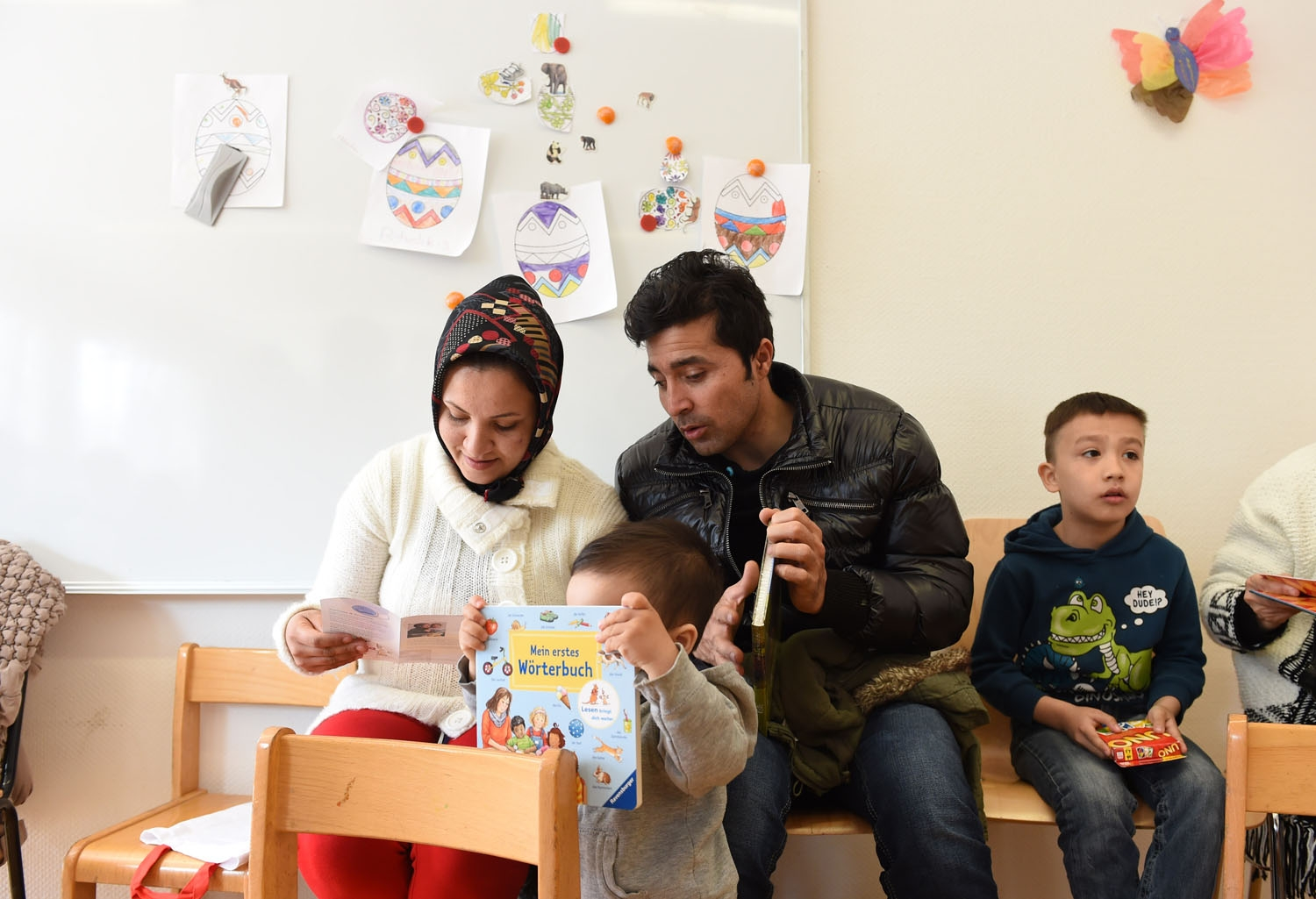 Refugee children and their parents from Afghanistan look at books and games during a first event of the three-year program reading start for refugee children in the refugee camp Bayernkaserne in Munich, southern Germany, on March 21, 2016