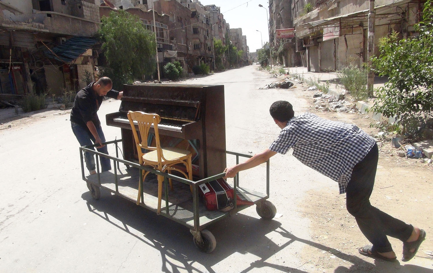 Ayham al-Ahmed (R), a resident of Damascus' Yarmuk Palestinian refugee camp, is helped by friends to push his piano in the middle of the street on June 26, 2014