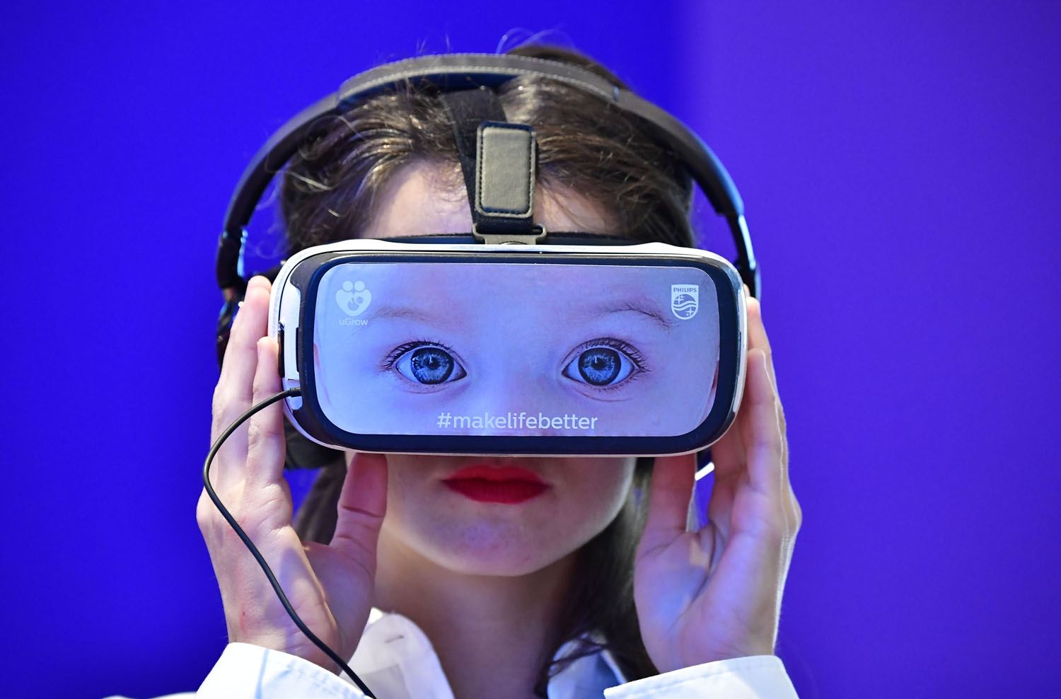 A fair worker presents VR glasses to promote baby surveillance systems at the booth of Philips at the IFA Consumer Electronics Fair in Berlin in Berlin on August 31, 2017.
