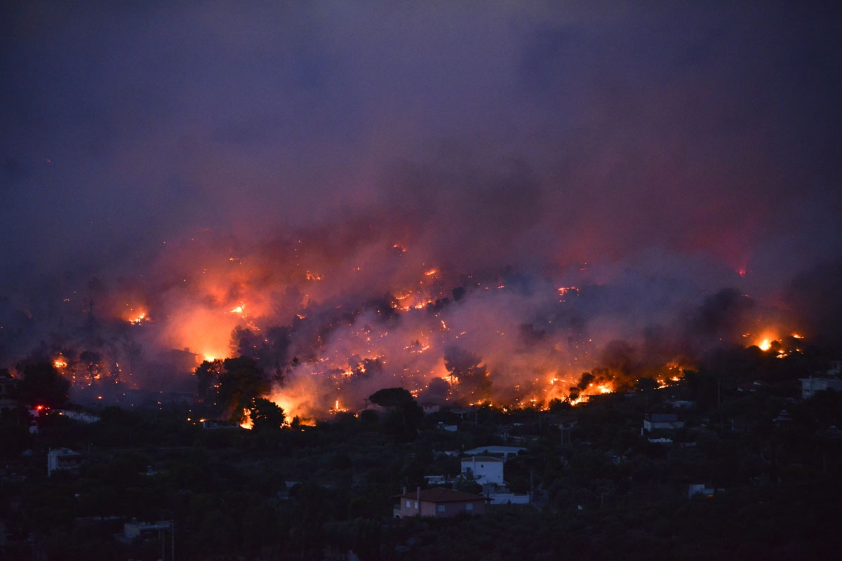 Flames rise as a wildfire burns in the town of Rafina, near Athens, on July 23, 2018.