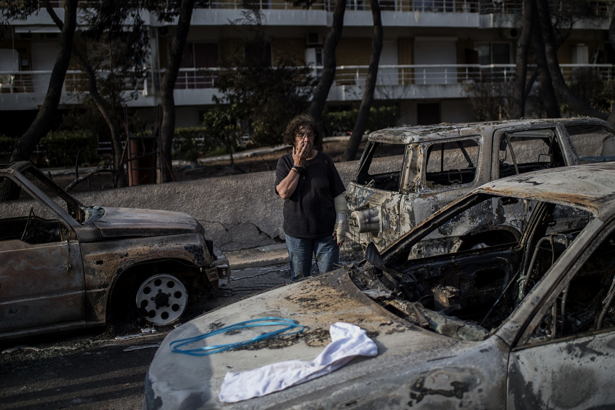 A woman with a cast stands among cars burnt following a wildfire at the village of Mati, near Athens, on July 24, 2018.