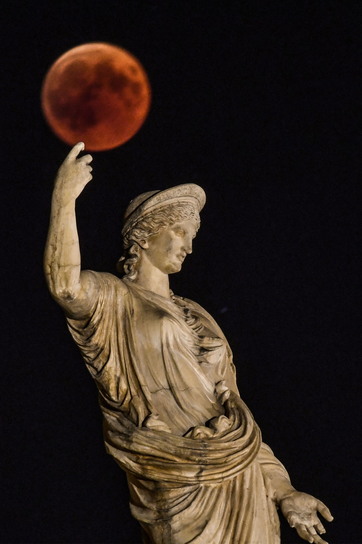 A picture shows the full moon during a blood moon eclipse beside a statue of the ancient Greek goddess Hera in central Athens on July 27, 2018.