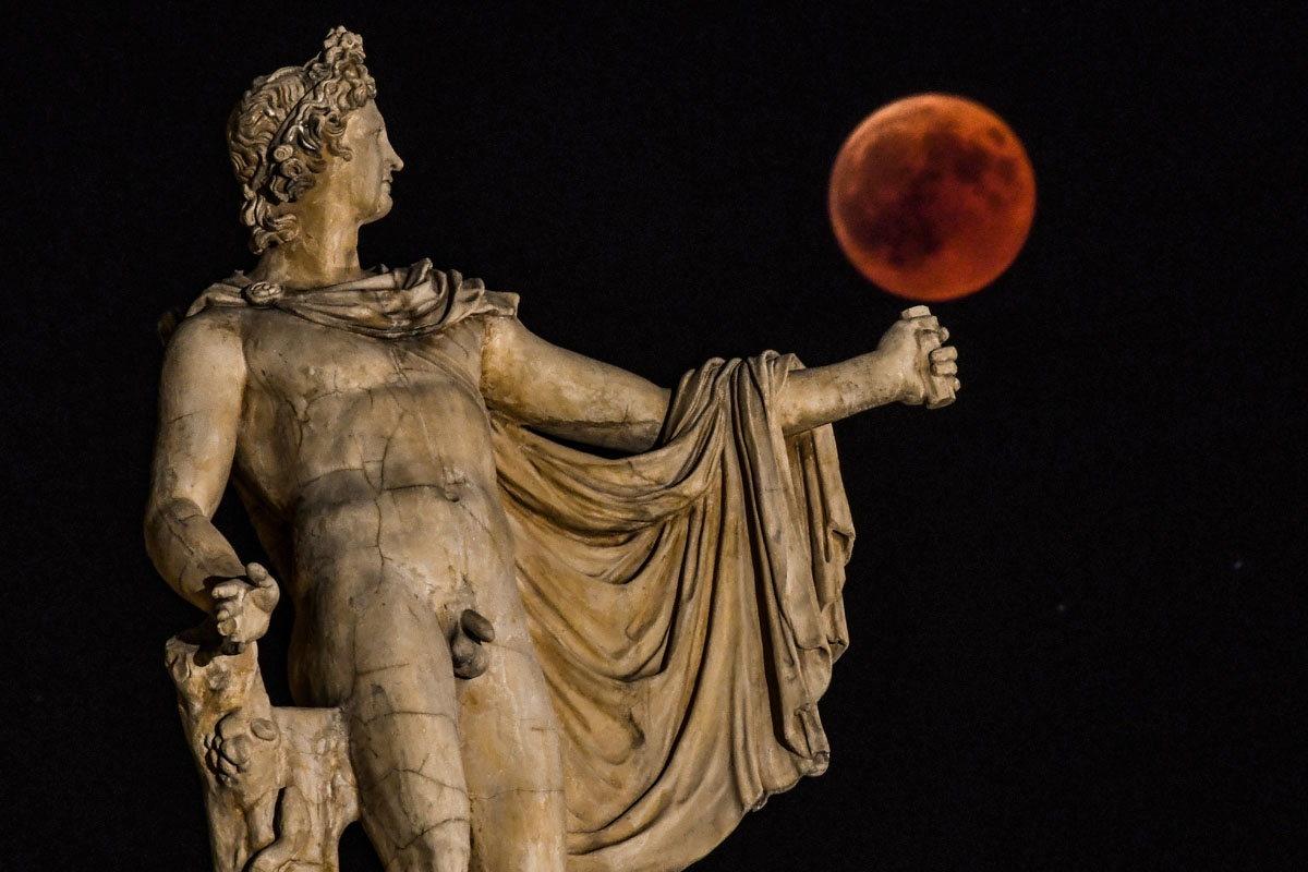 A picture shows the full moon during a blood moon eclipse beside a statue of the ancient Greek god Apollo  in central Athens on July 27, 2018.