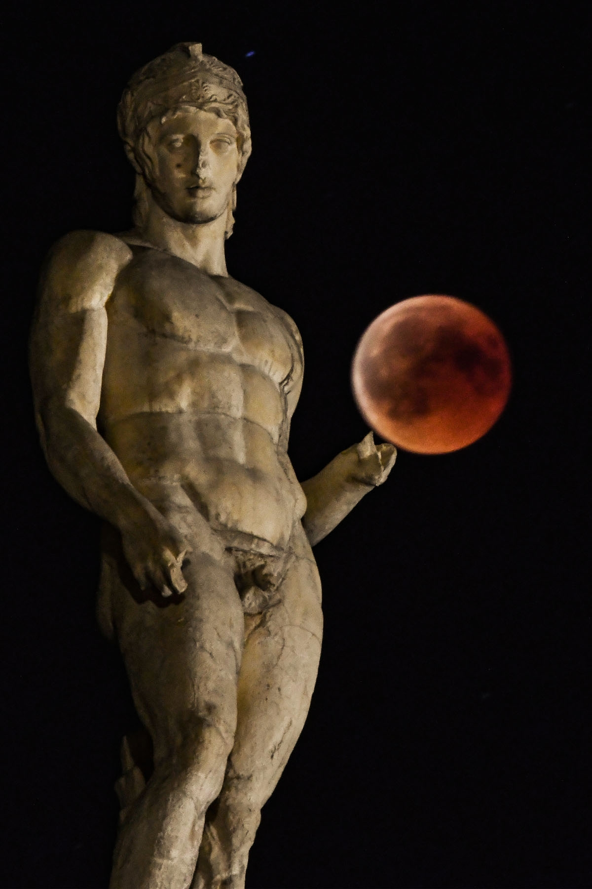 A picture shows the full moon during a blood moon eclipse beside a statue of ancient Greek god Ares in central Athens on July 27, 2018.