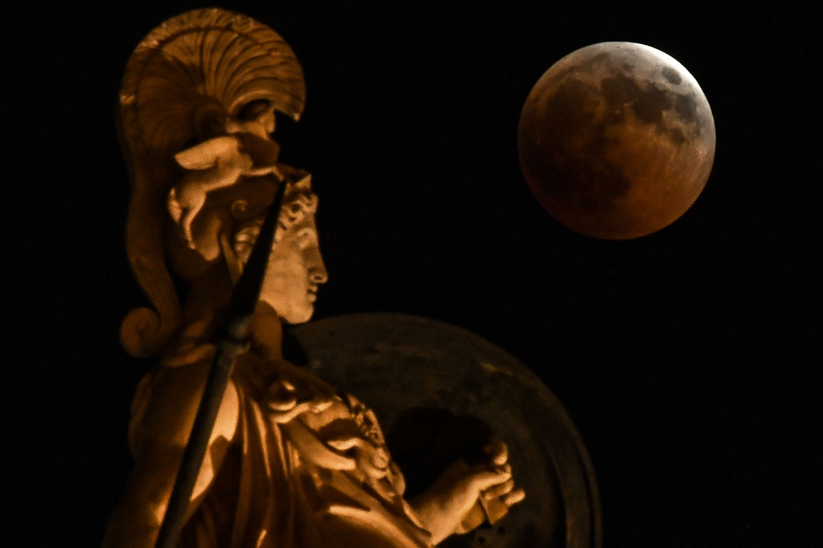 A picture shows the full moon during a blood moon eclipse beside a statue of ancient Greek goddess Athena in central Athens on July 27, 2018.