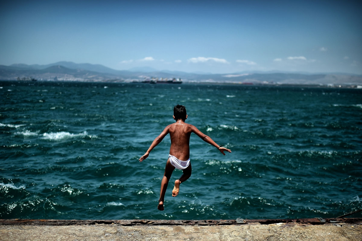 A young refugee jumps into the sea next to the refugee camp of Skaramangas in Athens on June 24, 2016.