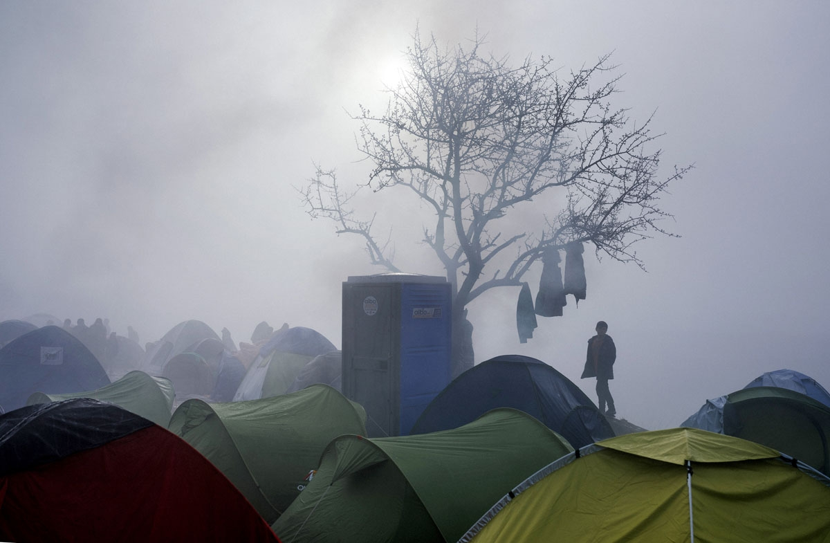 A boy stands among tents during a foggy morning at a makeshift camp at the Greek-Macedonian border near the Greek village of Idomeni on March 8, 2016, where thousands of refugees and migrants are trapped by the Balkan border blockade.