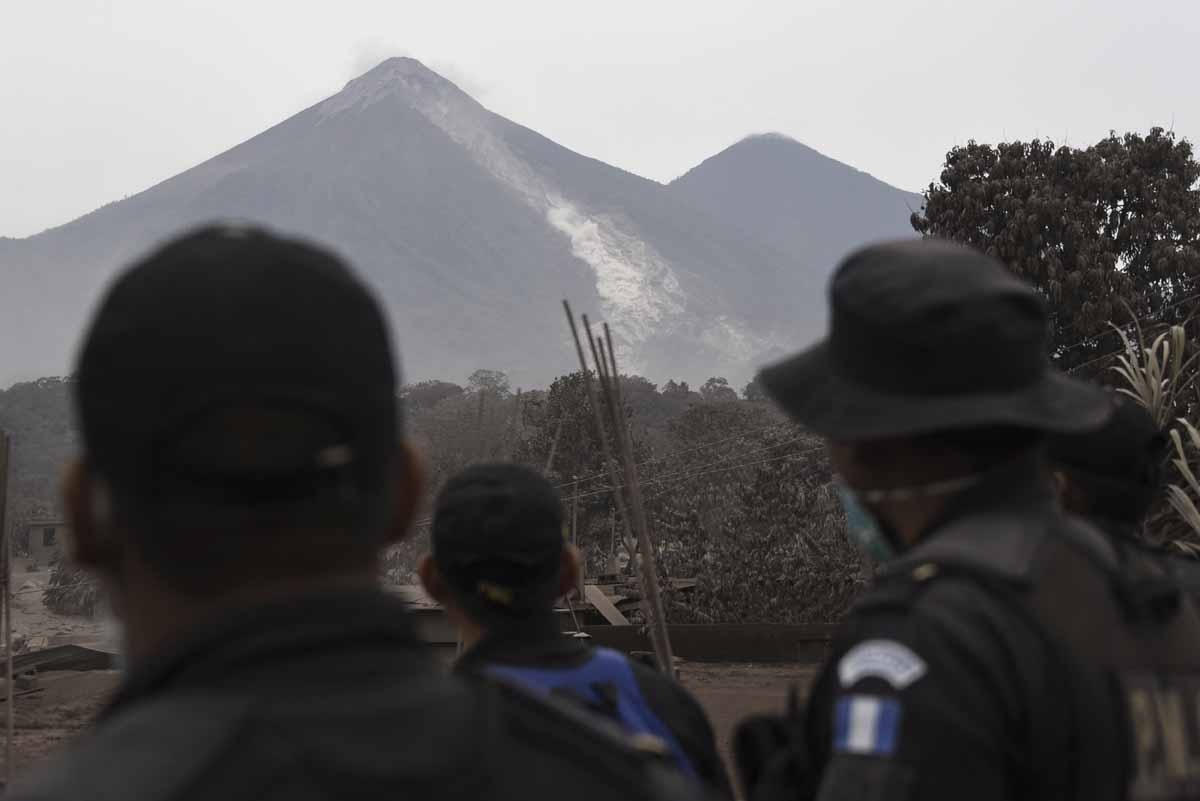 Police officers look at the Fuego Volcano from San Miguel Los Lotes, a village in Escuintla Department, about 35 km southwest of Guatemala City, on June 4, 2018, a day after an eruption. At least 25 people were killed, according to the National Coordinat