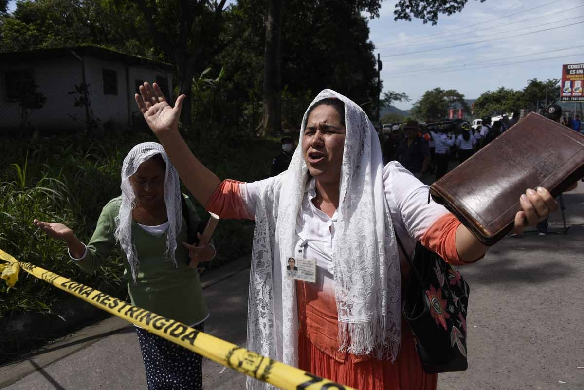 Two women praying at the entrance to the disaster zone in village of San Miguel Los Lotes, in Escuintla Department, about 35 km southwest of Guatemala City, on June 6, 2018. Nearly 200 people are missing and at least 75 have been killed since Guatemala's