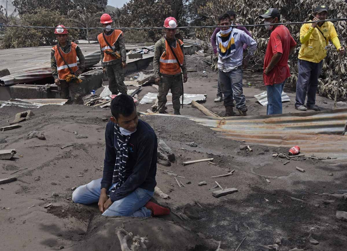 Bryan Rivera 22 year-odl cries during search relatives victims of the Fuego Volcano eruption in the ash-covered village of San Miguel Los Lotes, in Escuintla Department, about 35 km southwest of Guatemala City, on June 7, 2018. Nearly 200 people are missi