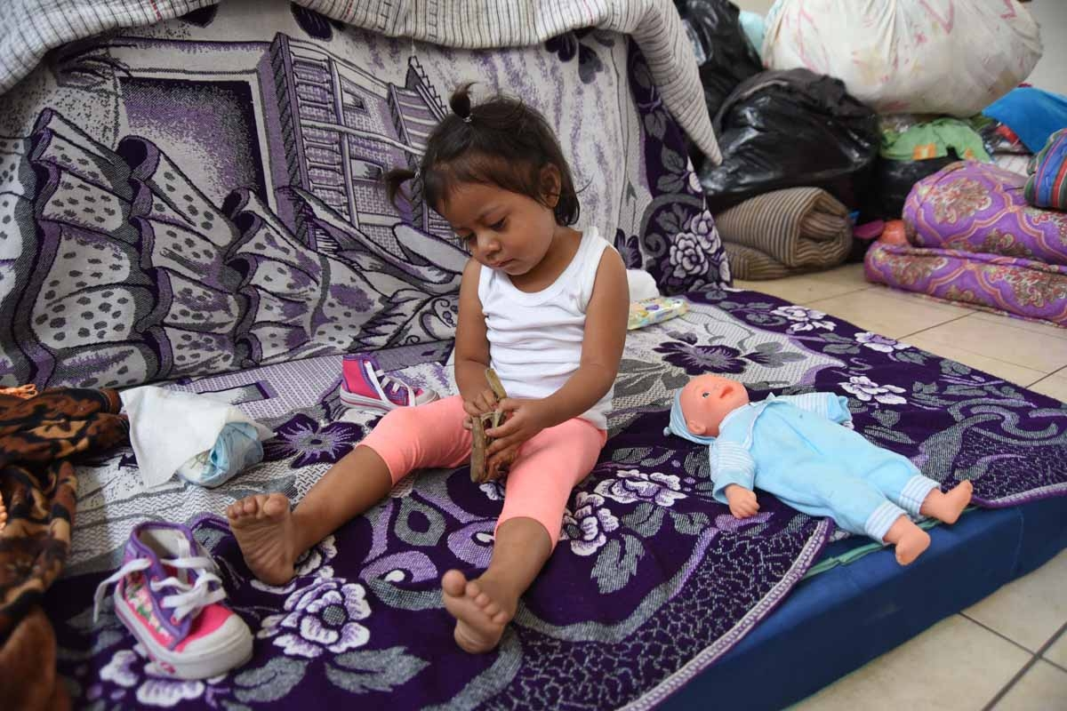 A girl plays in a temporary shelter in Escuintla department, 35 km south of Guatemala City on June 9, 2018. The threat of fresh landslides forced emergency workers Thursday to suspend a search for victims of a major eruption of Guatemala's Fuego Volcano,
