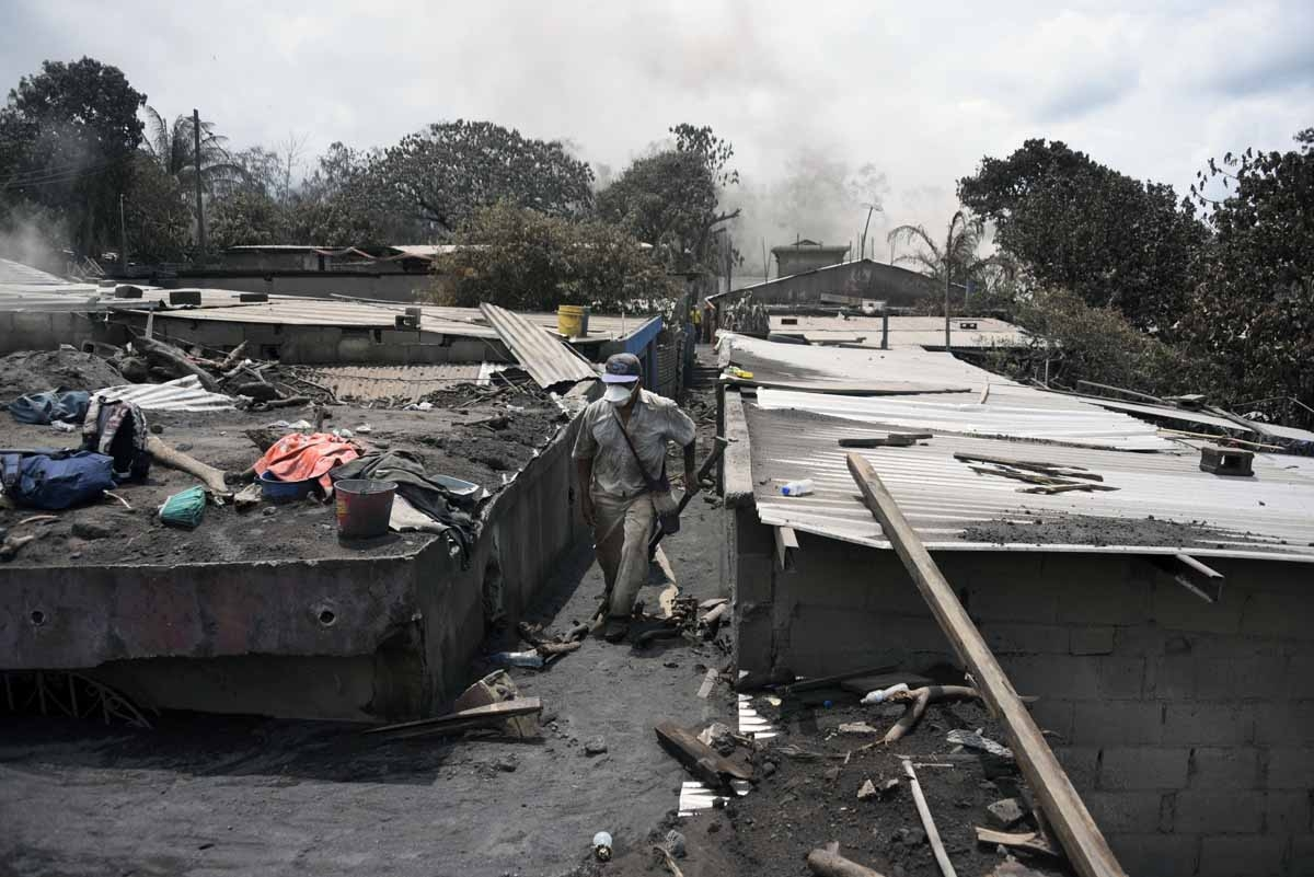 Residents search relatives victims of the Fuego Volcano eruption in the ash-covered village of San Miguel Los Lotes, in Escuintla Department, about 35 km southwest of Guatemala City, on June 7, 2018. Nearly 200 people are missing and at least 99 have been