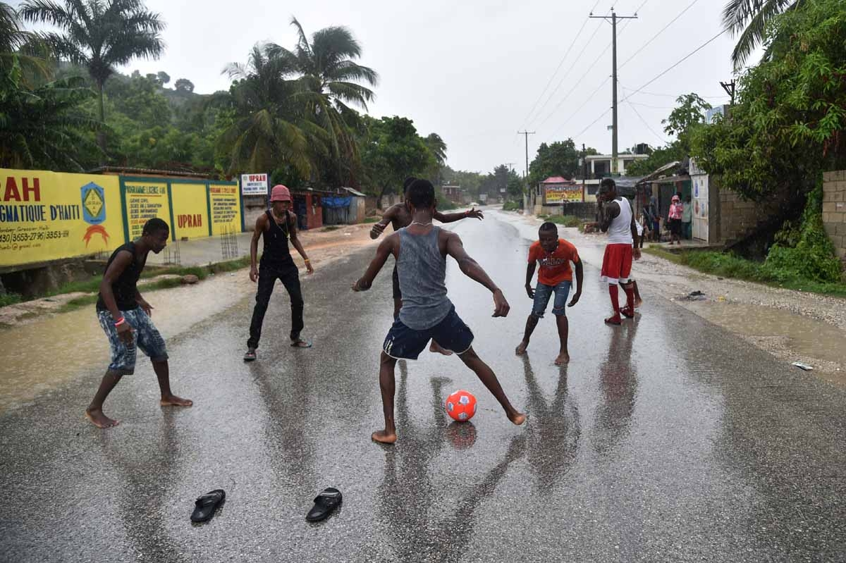 A group of young men play football in the rain on the route to Leogane, during the passing of the Hurricane Matthew, in Grassier, southwest of Port-au-Prince, on October 4, 2016.