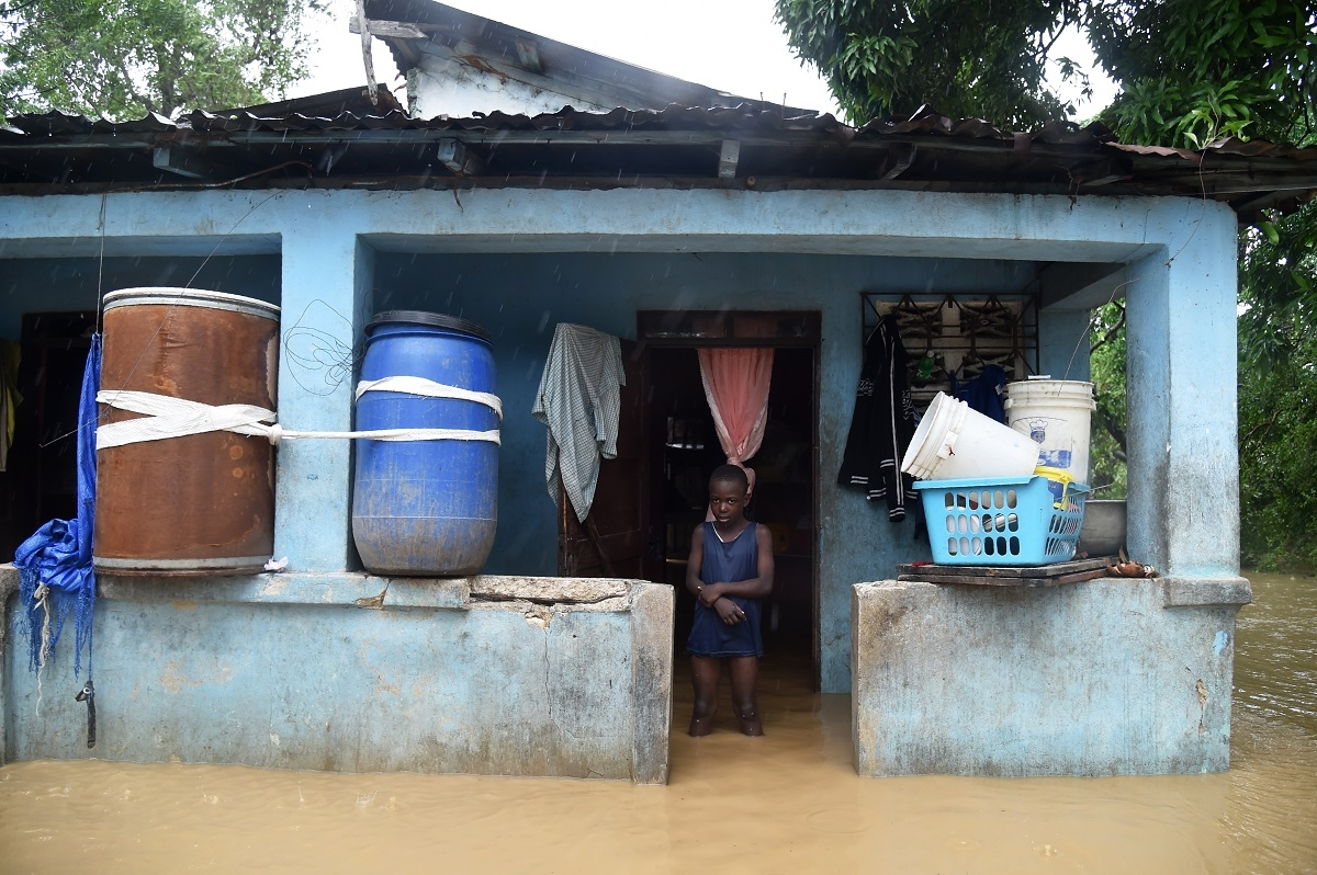 Franki stands in his flooded home following the overflowing of La Rouyonne river in the commune of Leogane, south of Port-au-Prince, October 5, 2016.