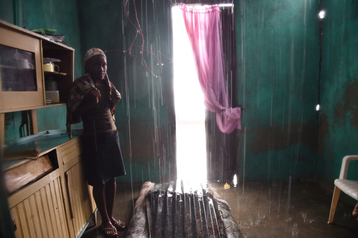 Judeline stands as the rain enters her house through the roof damaged by Hurricane Matthew, in Port-a-Pimet, Les Cayes, Haiti on October 14, 2016.