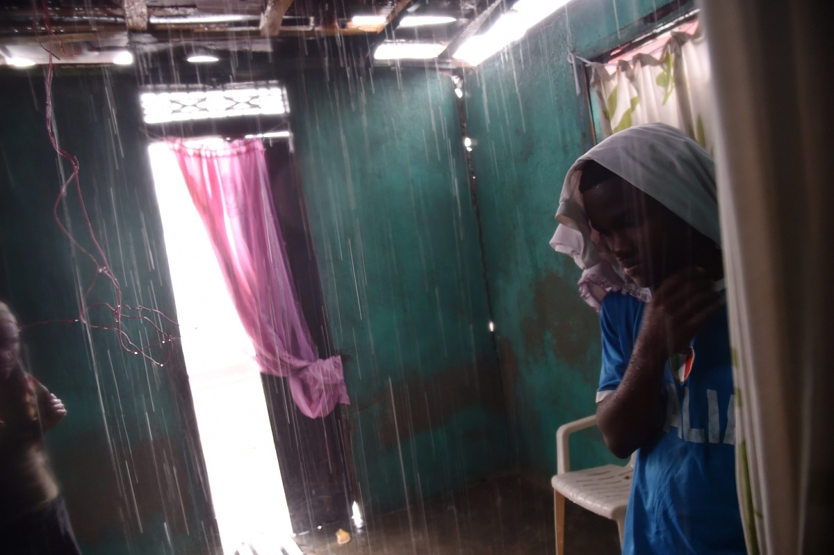 Judelin looks as the rain enters her house through the roof that was damaged by Hurricane Matthew, in Port-a-Pimet, Les Cayes, Haiti on October 14, 2016.