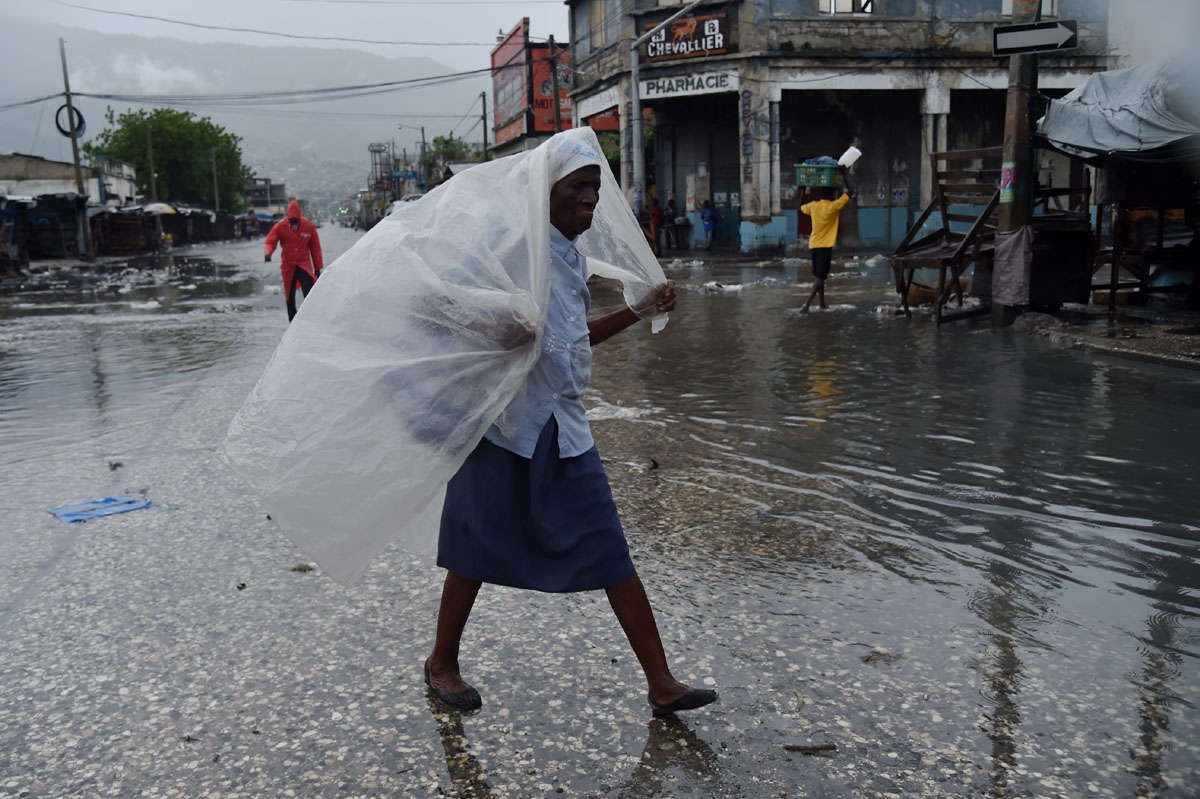 A woman protects herself from the rain with plastic after hurricane Matthew, in Port-au-Prince, on October 4, 2016.