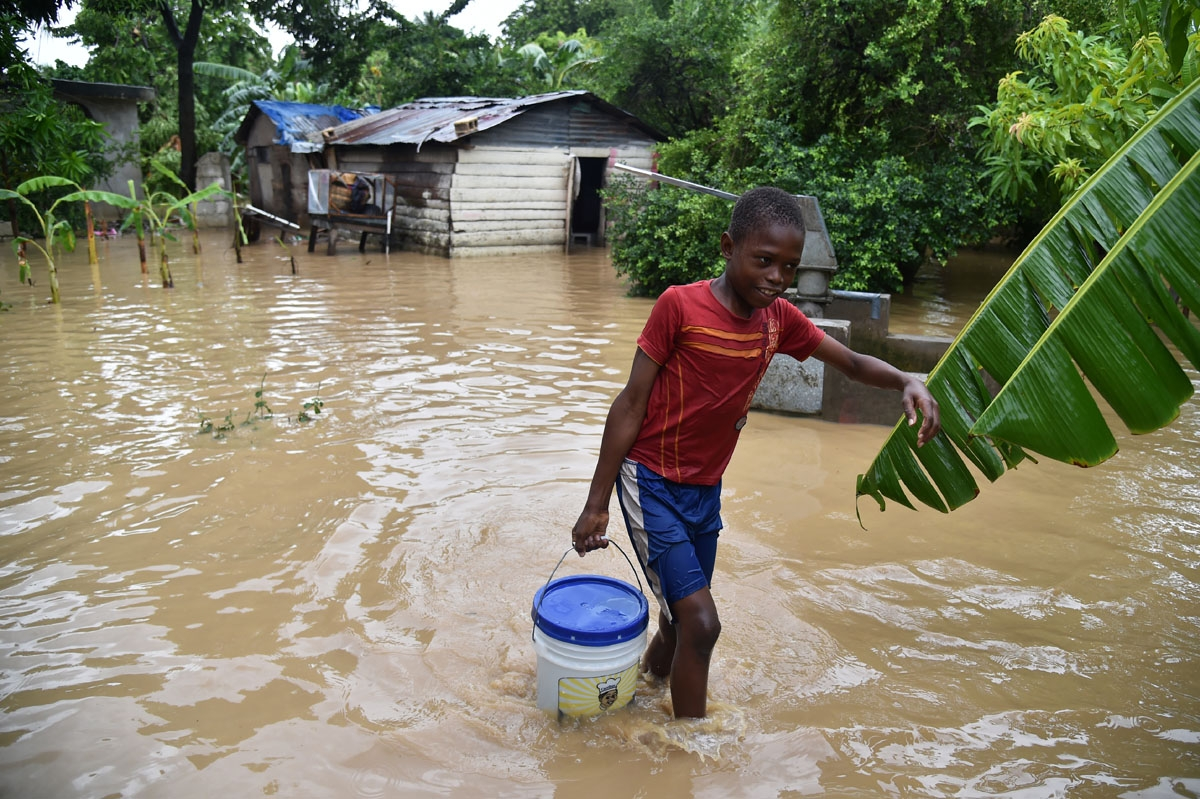 Jonnathan fetches clean water for his mother cleaning his home flooded by the overflowing of the La Rouyonne river in the commune of Leogane, south of Port-au-Prince, October 5, 2016.