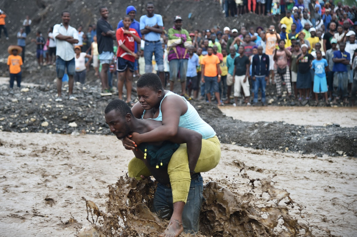 A man carries a woman across a  river at Petit Goave where a bridge collapsed during the rains of the Hurricane Matthew, southwest of Port-au-Prince, October 5, 2016.
