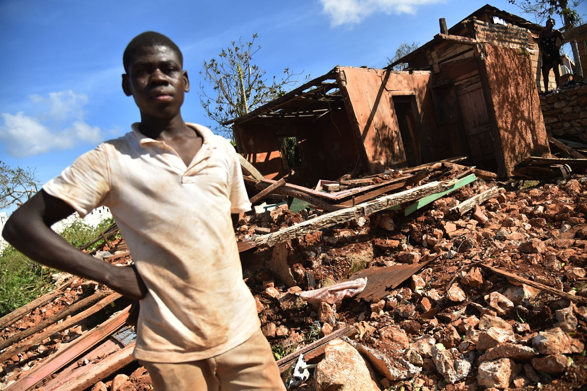 A young man stands in front of a home destroyed by Hurricane Matthew in the small village of Casanette, Haiti, on October 8, 2016.