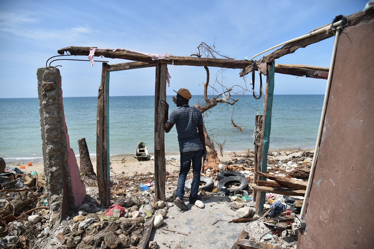 A man stands next to a destroyed house in Les Cayes, Haiti on October 10, 2016, following the passage of Hurricane Matthew.