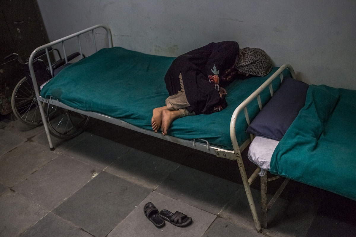 In this photo taken on November 20, 2015, Kashmiri patient Masrat Naz, 45, and who is suffering from symptoms of schizophrenia, lies on a bed as she periodically shouts to medical staff after being brought by relatives to the casualty ward at the Psychiat