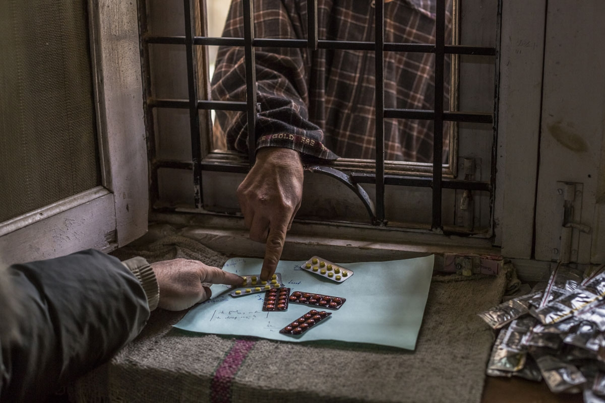 In this photo taken on December 4, 2015, a Kashmiri patient suffering from symptoms of depression reaches through a barred window to collect a repeat prescription for range of anti-depressants at the dispensary at the Psychiatric Diseases government hospi