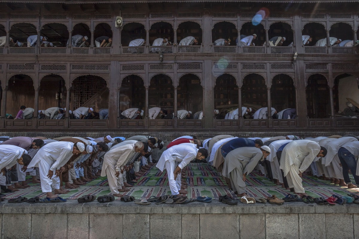 In this photo taken on September 9, 2016, Kashmiri Muslims offer prayers to mark the urs, or death-anniversary, of Sufi scholar Mir Syed Ali Hamden at the Shah-i-Hamdan shrine, amid an ongoing curfew and strike, on the banks of the Jhelum River in Srinaga
