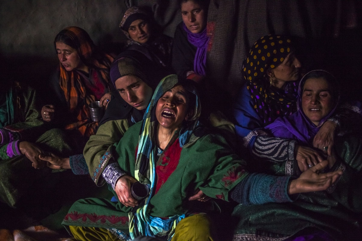 In this photo taken on December 14, 2015, Kashmiri relative Hafeeza Khan (C) weeps during the funeral of nephew Rasiq Ahmed Khan, aged around 22, and who was found shot to death, at their home in Watchohallan village in south Kashmir's Shopian district so