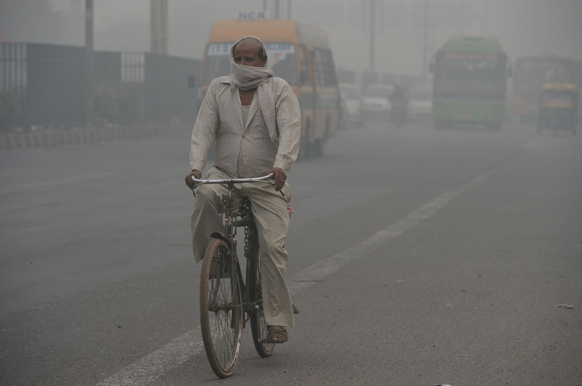 A cyclist covers his face while riding along a major road as smog covers the capital's skyline in New Delhi on November 2, 2016.
