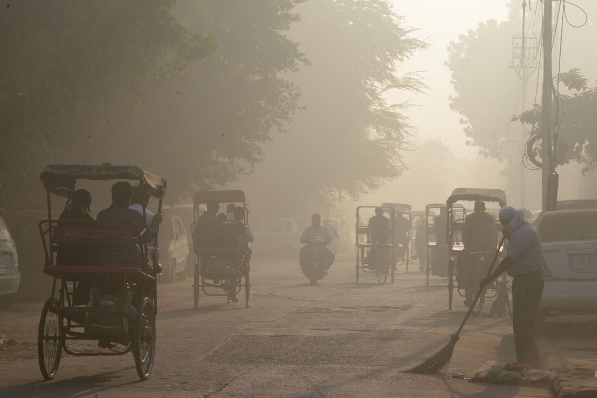 An Indian worker sweeps as smog envelops a street in the old quarters of New Delhi on November 3, 2016.