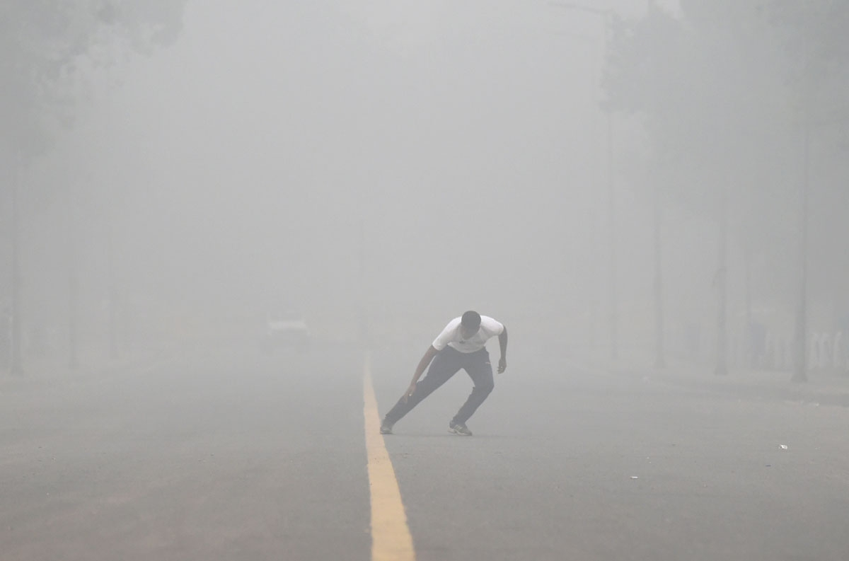 An Indian man does morning exercises on a road as heavy smog covers New Delhi on November 7, 2016.