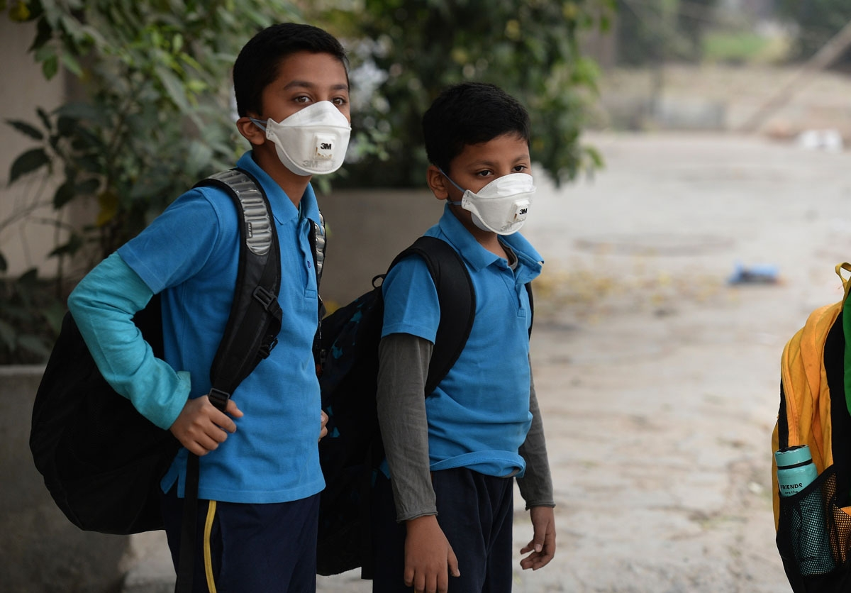 Indian school children wear masks as they wait for the bus as schools re-open after three days of closure due to smog, in New Delhi on November 10, 2016. / AFP PHOTO / PRAKASH SINGH