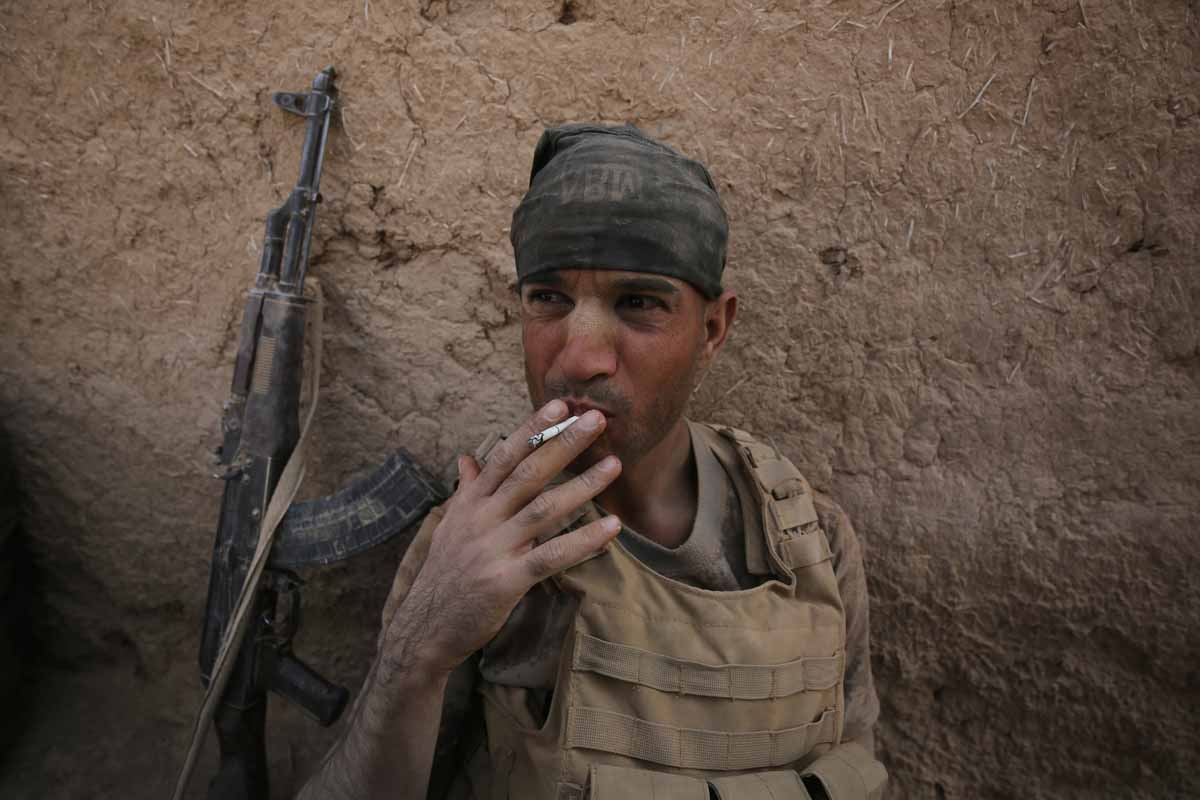 A member of the Iraqi government forces smokes a cigarette as they rest in the village of al-Khuwayn, south of Mosul, after recapturing it from Islamic State (IS) group jihadists on October 23, 2016, in part of an ongoing operation to tighten the noose ar
