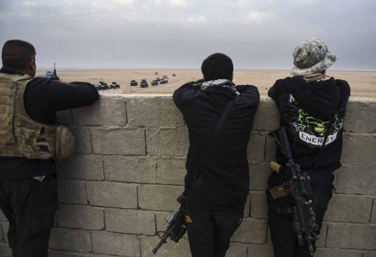 Members of the Iraqi Counter Terrorism Service (CTS) look out at their comrades driving near the village of Bazwaya, on the eastern edges of Mosul, as they advance towards Iraq's last remaining Islamic State (IS) group stronghold on October 31, 2016.