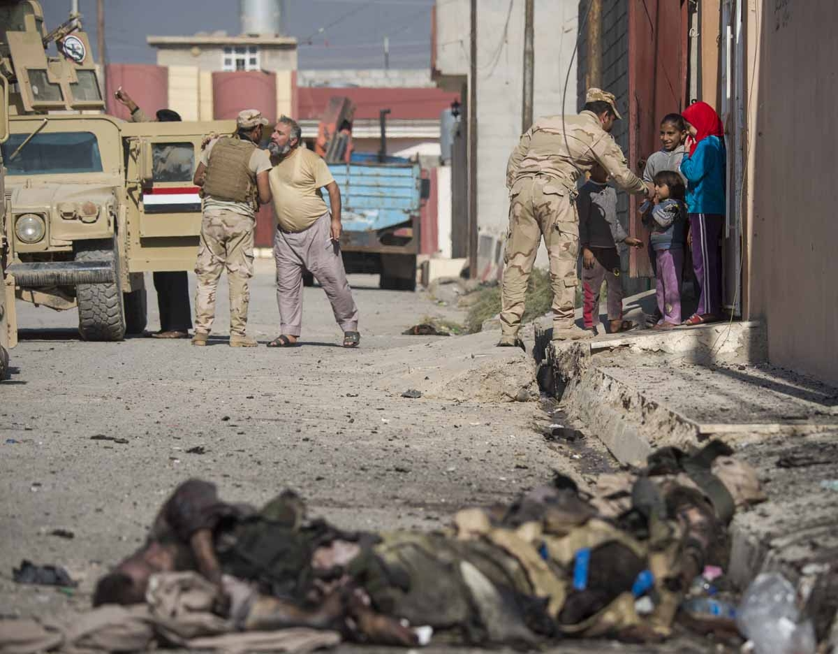 Soldiers from the Iraqi army 9th armoured division greet residents as bodies of Islamic State (IS) group fighters litter a street in the eastern Al-Intissar neighbourhood of Mosul on November 6, 2016.
