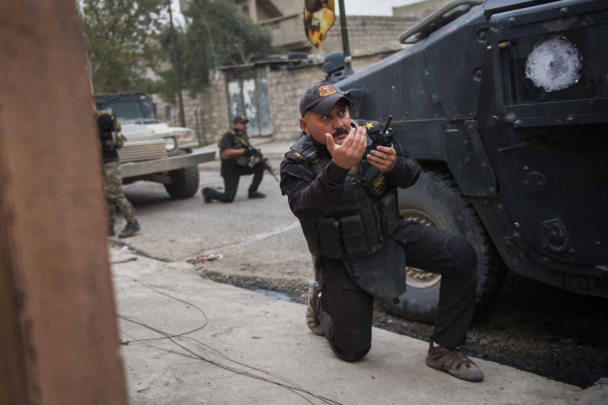 A commander from the Iraqi Special Forces 2nd division calls his men back to a previous position as they come under fire from IS fighters while pushing into the Aden neighbourhood in Mosul on November 16, 2016.