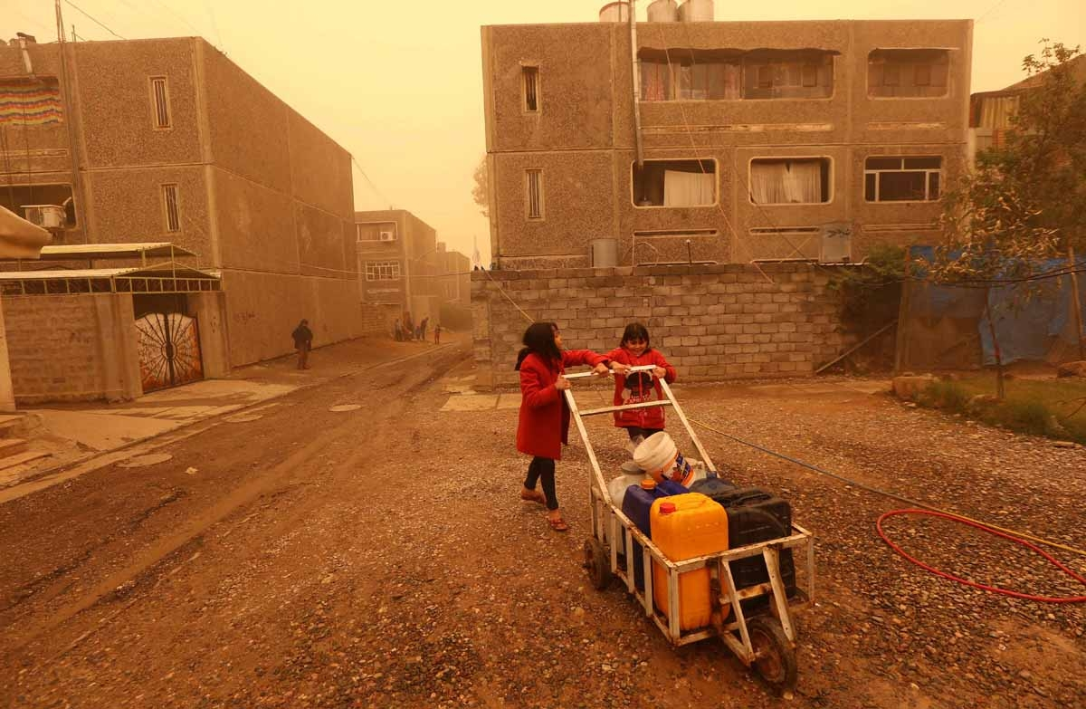 Iraqi girl wait to fill jerricans with water in Mosul's eastern district of Khadraa, on December 2, 2016.