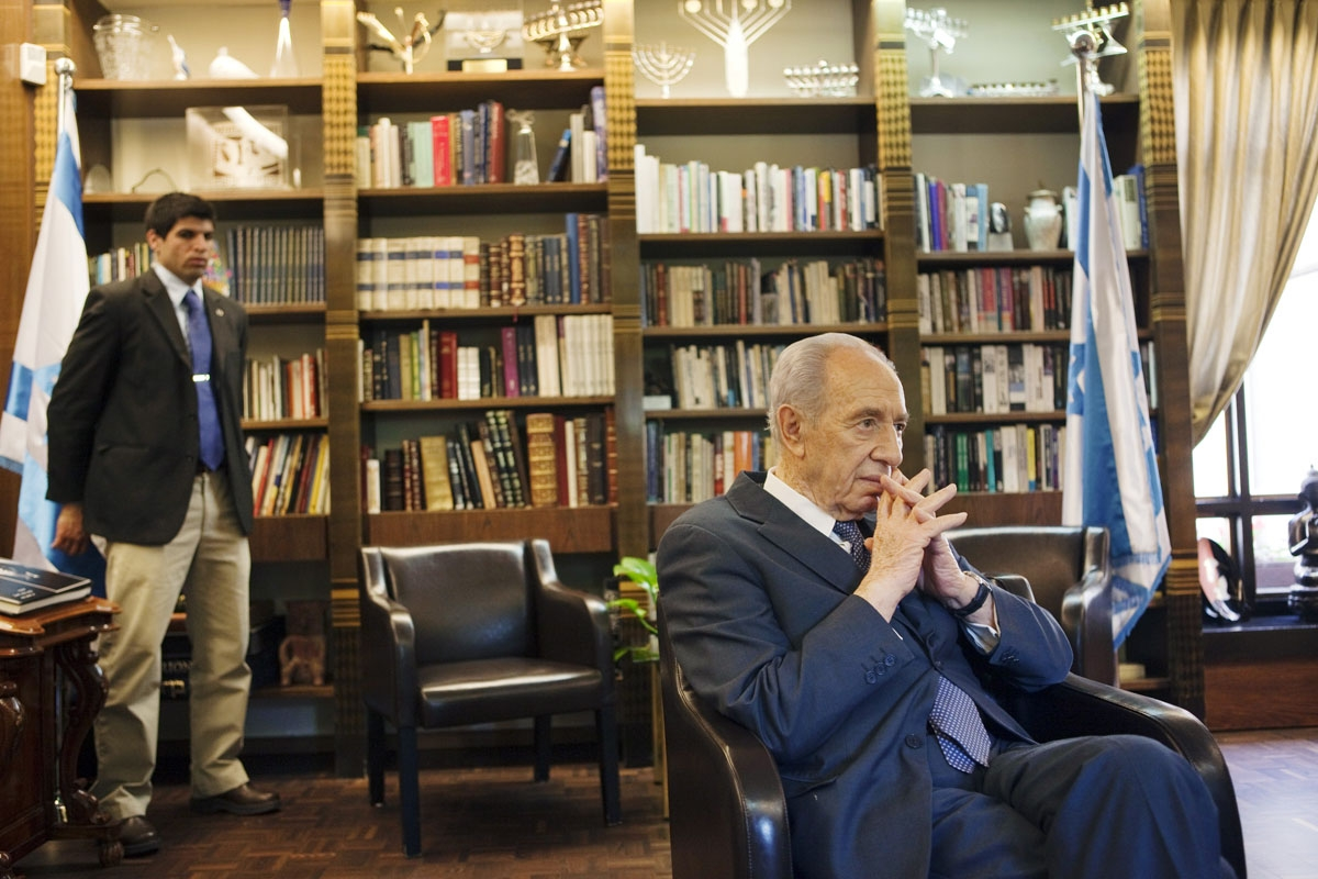 Israeli President Shimon Peres answers journalist question during an interview on April 6, 2010 in his residency in Jerusalem while his bodyguard looks on