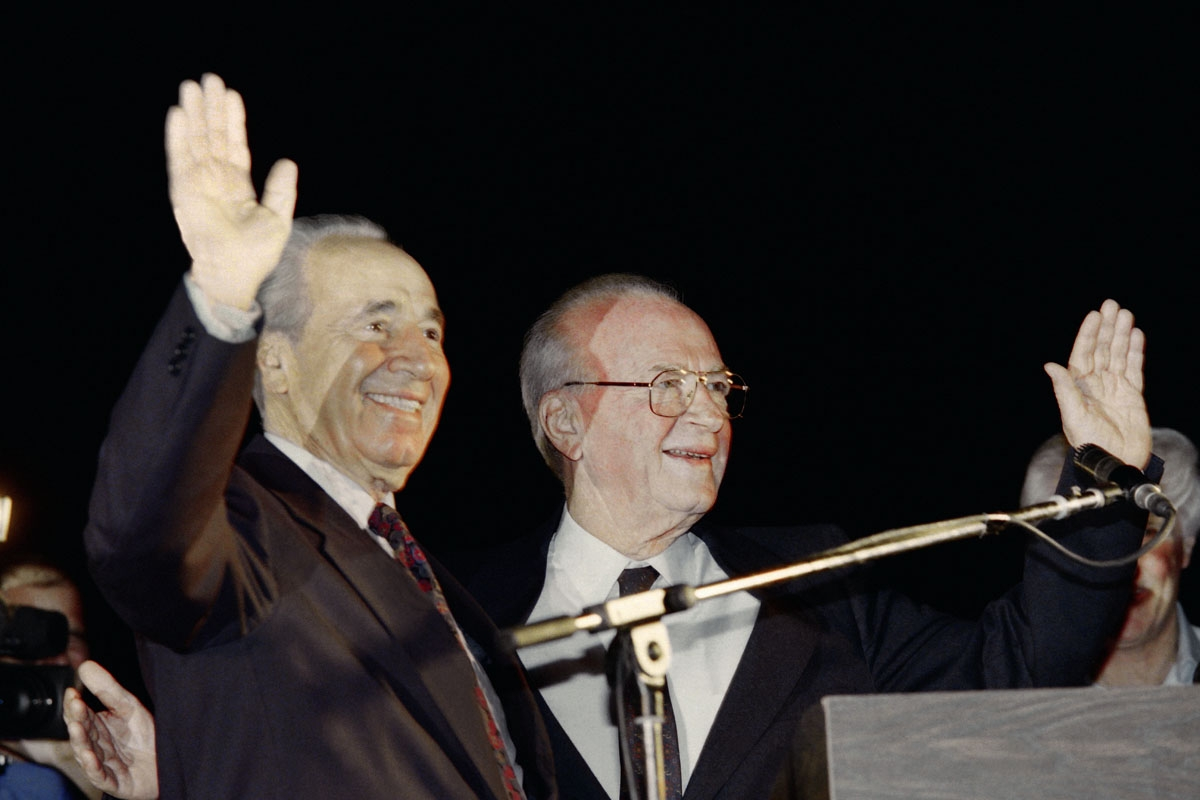 Israeli Prime Minister Yitzhak Rabin (R) and Foreign Minister Shimon Peres wave to a crowd of more than 100,000 Israelis who gathered for a Yes to Peace rally in Tel Aviv on November 4, 1995