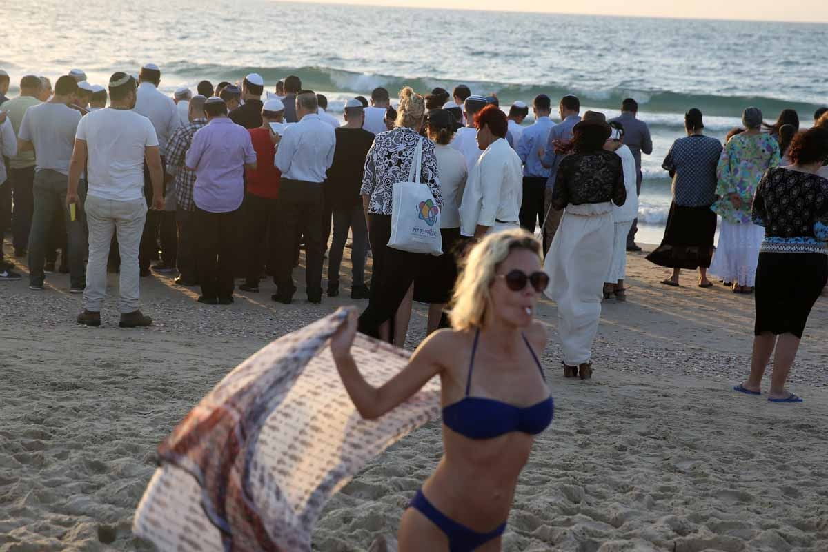 Orthodox Jews (in the background) pray in front of the Mediterranean Sea on October 3 2016 in the Israeli city of Ashdod, south of Tel Aviv, during the Tashlich ritual.