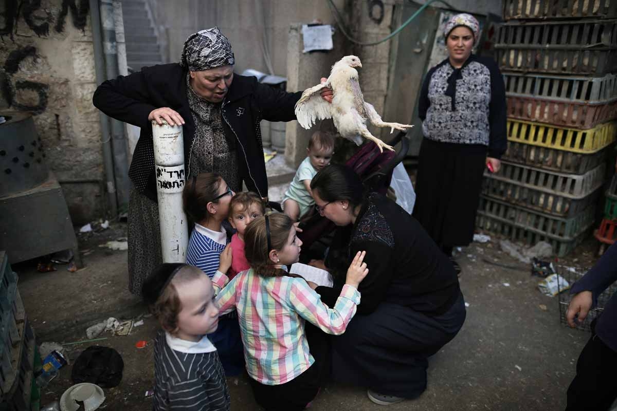 An ultra-Orthodox Jewish woman swings a chicken over her family as they perform the Kapparot ceremony in the ultra-Orthodox neighbourhood of Mea Shearim in Jerusalem on October 10, 2016.