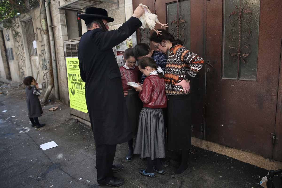 An Ultra-Orthodox Jewish man swings a chicken over his family as they perform the Kapparot ceremony in the ultra-Orthodox neighbourhood of Mea Shearim in Jerusalem on October 10, 2016.